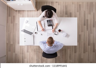 High Angle View Of Two Businesspeople Analyzing Bill In Office