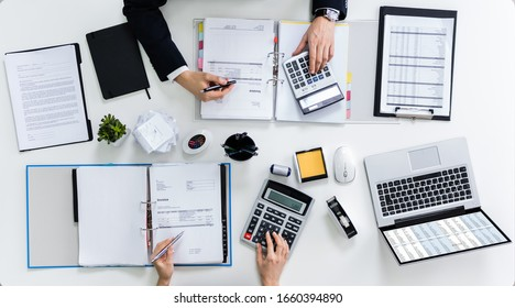 High Angle View Of Two Businesspeople Calculating Bills In Office