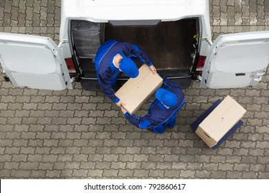 High Angle View Of Two Delivery Men Unloading Cardboard Box From Truck