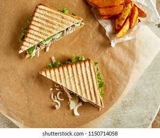 High angle view of two grilled sandwiches, served on backing paper with fried crispy potato