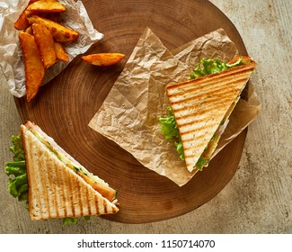 High angle view of two grilled sandwiches,  served on wood with fried crispy potato
