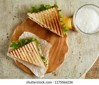 High angle view of two grilled sandwiches, served on backing paper with glass of beer