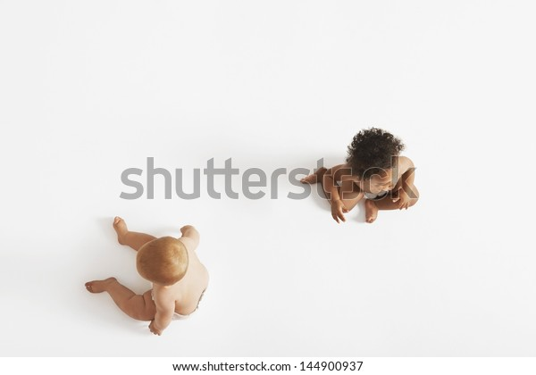 High angle view of two multiethnic babies looking in different directions isolated on white background