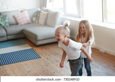 High angle view of two sweet happy Caucasian children siblings girl and boy playing tag at home, chasing each other in light spacious living room, being home alone. Childhood, joy, fun and happiness