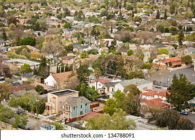A high angle view of a typical housing area in an urban area with a variety of residential buildings, including two Victorian style houses in the foreground. San Jose, California.
