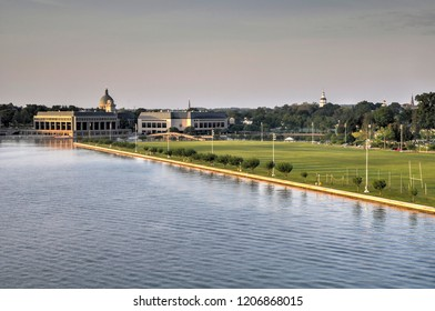 High angle view of the United States Naval Academy in Annapolis from the Severn River. The Chapel dome and the Maryland State House dome stand above the horizon line.