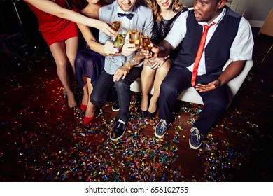 High angle view of unrecognizable group of friends toasting with champagne flutes while celebrating momentous event at night club, floor covered with colorful confetti