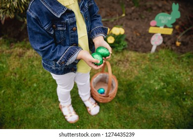 HIgh angle view of an unrecognsiable child. They are holding their hands together, cupped, with chocolate easter eggs inside. She has a basket at her feet with some more easter eggs in.