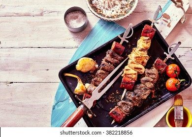High Angle View of Variety of Grilled Meat Skewers Surrounded by Fresh Ingredients and Sauces and Served on Pan Placed on Rustic Wooden Paddle, Still Life with Copy Space