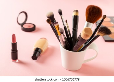 High angle view of various make up products on pink background. Make up brushes, liquid face powder, blush, lipstick and eyeshadow palette on pink background