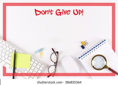 High Angle View of Various Office Supplies on Desk with a phrase Don't Give Up!