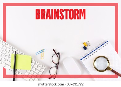 High angle view of various office supplies on desk with a word BRAINSTORM