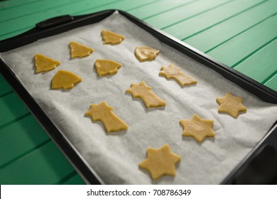 High angle view of various shape raw cookies in baking tray on wooden table