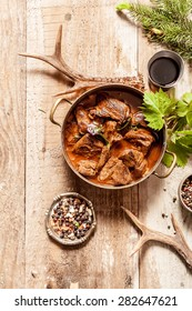High Angle View of Venison Goulash Stew in Pot with Seasoning on Wooden Surface Surrounded by Deer Antlers and Tree Sprigs