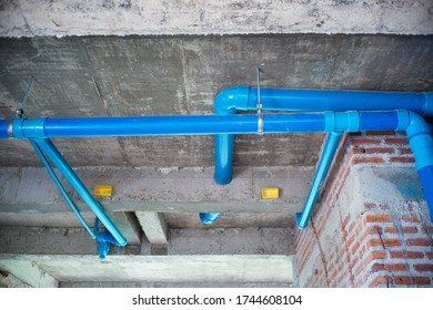 High angle view of water pipes line hanging from the concrete ceiling in the house under construction. Water distribution system