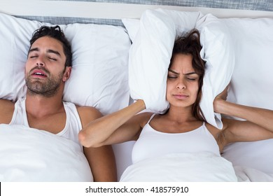 High angle view of woman blocking ears while man snoring on bed