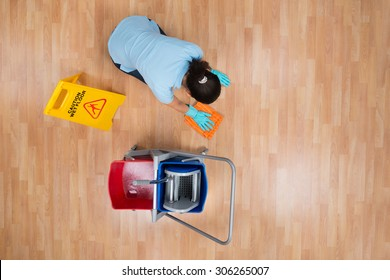 High Angle View Of Woman Cleaning Floor With Rag