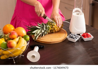 High angle view of a woman cutting a pineapple top with a kitchen knife on a cutting board in order to peel it with a pineapple cutter