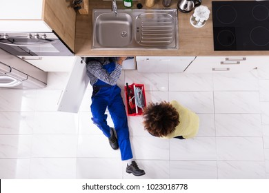 High Angle View Of Woman Looking At Plumber Repairing Sink In Kitchen