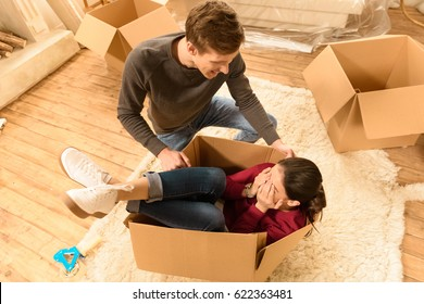 high angle view of woman and man having fun at new home
