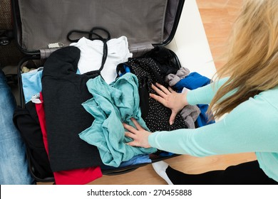 High Angle View Of Woman Packing Clothes In Suitcase