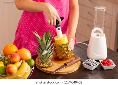 High angle view of a woman peeling a pineapple with a pineapple cutter, making a fresh, healthy, raw fruit smoothie