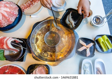 High angle view of woman putting shrimp into the hotpot
