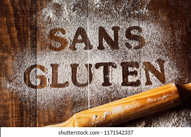 high angle view of a wooden table sprinkled with a gluten free flour where you can read the text sans gluten, gluten free written in french, next to a rolling pin