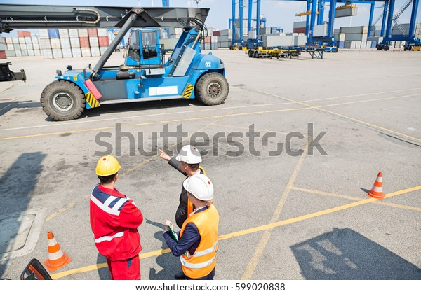 High angle view of workers discussing in shipping yard