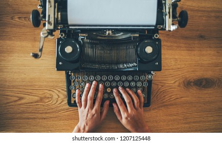 High angle view of writer's hands prints on vintage typewriter