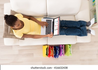 High Angle View Of Young African Woman Sitting On Sofa Shopping Online With Debit Card