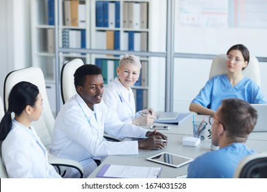 High angle view at young African-American doctor speaking during medical conference and smiling happily, copy space