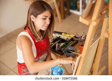 High angle view of a young artist wearing an apron and working on a painting in her studio