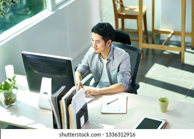 high angle view of young asian business person working in office using desktop computer