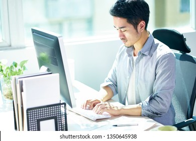 high angle view of a young asian businessman entrepreneur working in office using desktop computer.