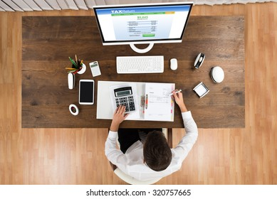 High Angle View Of Young Businessman Calculating Tax With Computer At Desk