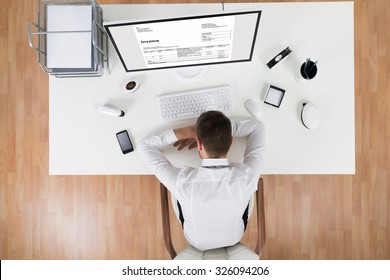 High Angle View Of Young Businessman Sleeping In Front Of Computer At Desk
