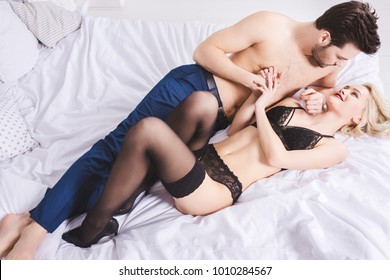 high angle view of young couple looking at each other while lying together in foreplay on bed