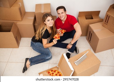 High angle view of a young couple unpacking boxes in a new home and eating some pizza together