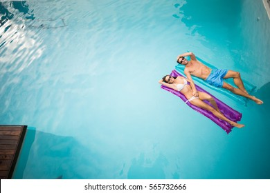 High angle view of young couple relaxing on inflatable raft at swimming pool
