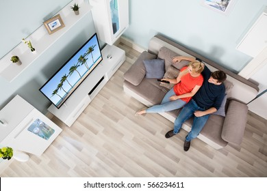 High Angle View Of Young Couple Sitting On Couch Watching Television Together At Home