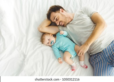 High angle view of young father laying in bed with infant daughter