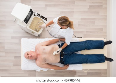 High Angle View Of A Young Female Doctor Using Ultrasound On Abdomen Of Senior Patient