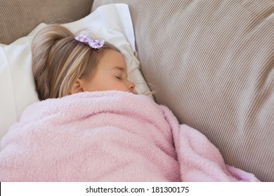 High angle view of a young girl sleeping on sofa in the living room at home