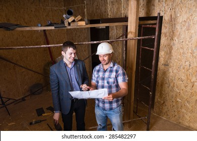 High Angle View of Young Male Architect and Construction Worker Foreman Inspecting Building Plans Together Inside Unfinished Building