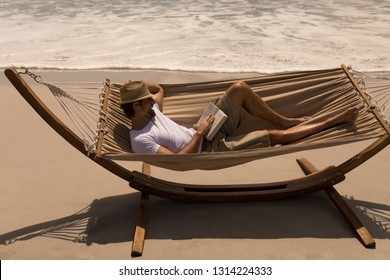 High angle view of young man with hat reading a book while relaxing on hammock at beach in the sunshine