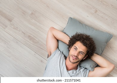 High Angle View Of Young Man Lying On Floor Thinking