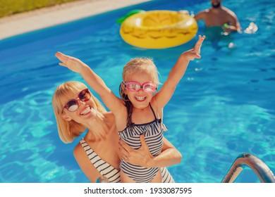 Grosser Ausblick auf die junge Mutter, die sich mit ihrer Tochter im Swimmingpool amüsiert hat, den heißen Sommertag im Freien genießt und sich im Urlaub entspannen