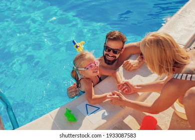 High angle view of young parents having fun playing with their daughter in the swimming pool, enjoying hot sunny summer day outdoors and relaxing while on a vacation