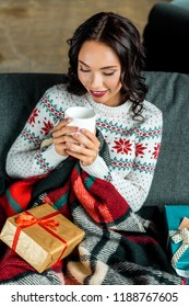 high angle view of  young woman holding coffee cup and sitting on sofa under blanket with christmas gift boxes at home